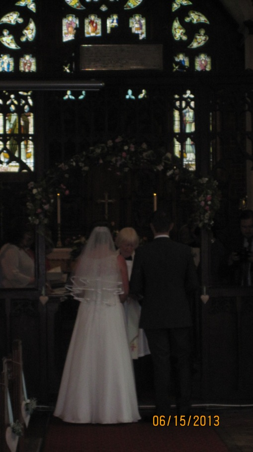 Mr and Mrs Rawlinson exchanging vows at All Saints Church, Rayne